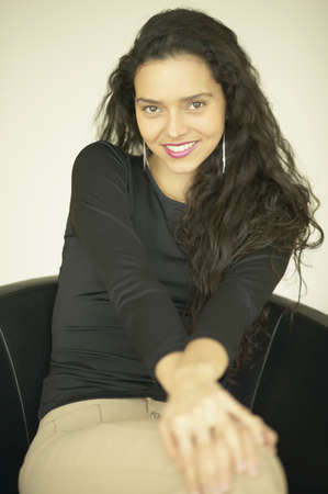 three persons only: Hispanic woman sitting in chair smiling