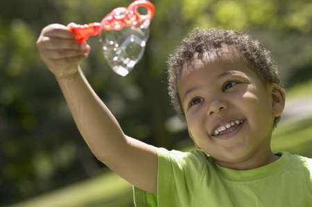 jamaican ethnicity: African boy playing with bubbles LANG_EVOIMAGES