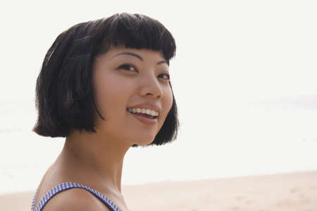children face: Close up of Asian woman at beach LANG_EVOIMAGES