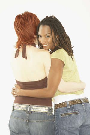 three persons only: Studio shot of female couple hugging