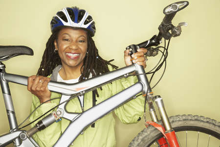 middleaged: Middle-aged African woman holding bicycle