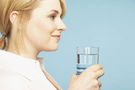 daydreamer: Young woman holding glass of water