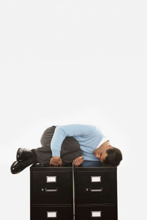 filing: Businessman sleeping on top of filing cabinet LANG_EVOIMAGES