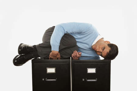 seriousness skill: Businessman in fetal position on top of filing cabinet