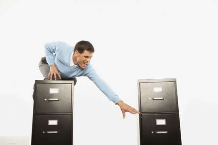 wearying: Businessman on top of filing cabinet reaching for other filing cabinet