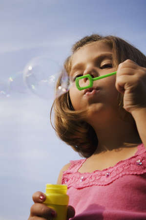 exerting: Low angle view of girl blowing bubbles LANG_EVOIMAGES