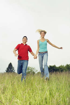 solicitous: Couple running in meadow LANG_EVOIMAGES
