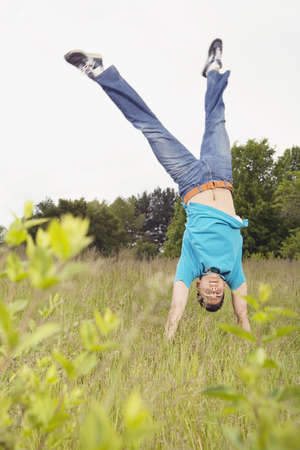 daydreamer: Young man performing handstand in meadow