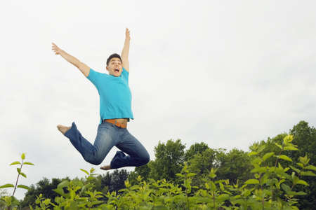 Young man jumping in meadow