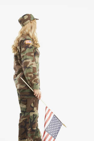 valor: Woman wearing military uniform and holding American flag LANG_EVOIMAGES