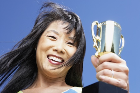 low angle view: Low angle view of Asian woman holding trophy LANG_EVOIMAGES