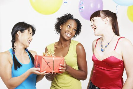 africanamerican: Three woman holding gift at party LANG_EVOIMAGES