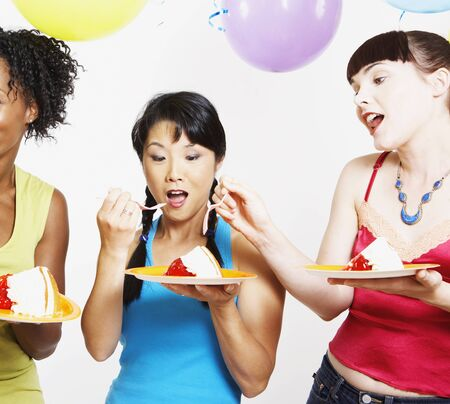 Three women eating cake at party