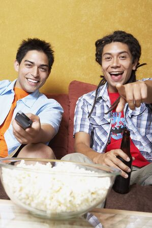 three persons only: Two Hispanic men watching television