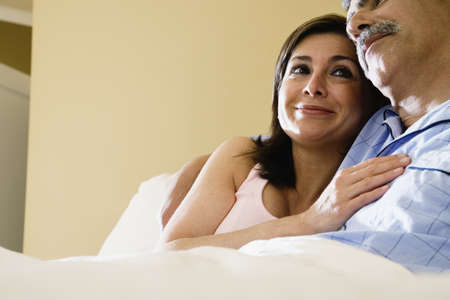 Middle-aged couple hugging in bed Stock Photo