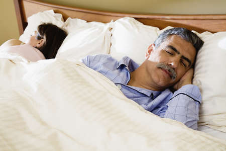 bedcover: Middle-aged couple sleeping in bed LANG_EVOIMAGES