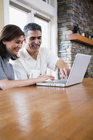 mischeif: Middle-aged couple typing on laptop LANG_EVOIMAGES
