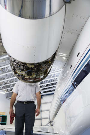 longshot: Repairman standing behind airplane engine LANG_EVOIMAGES