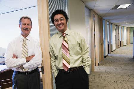unyielding: Portrait of two businessmen in doorway of office