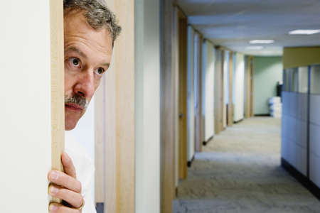 three persons only: Middle-aged businessman peeking out of office doorway LANG_EVOIMAGES