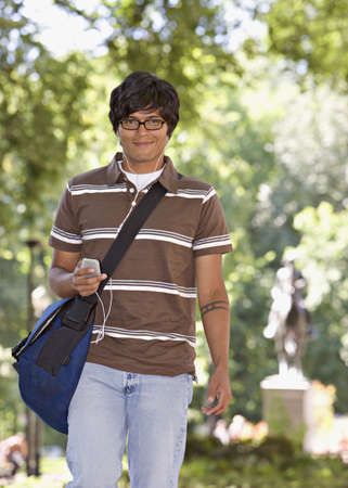 casualness: Indian man carrying book bag outdoors LANG_EVOIMAGES
