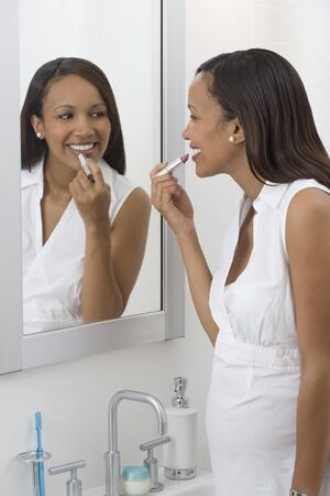 women only: Pregnant African woman applying lipstick in mirror
