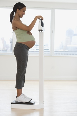 woman closet: Pregnant African woman on scale