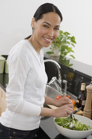 idealistic: African woman making salad in kitchen