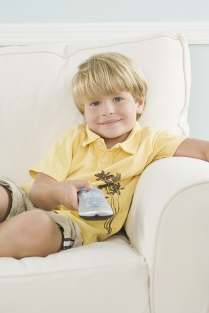 spectating: Young boy on sofa pointing remote control
