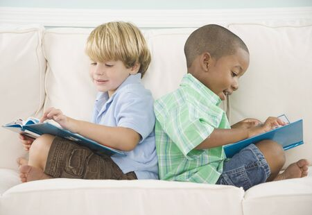 fond of children: Two young boys reading on sofa LANG_EVOIMAGES