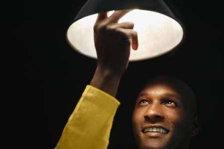 generation gap: African man changing light bulb LANG_EVOIMAGES