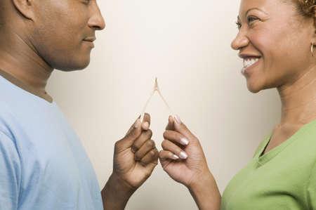eyes downcast: African couple holding wishbone