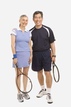 exerting: Senior couple holding tennis rackets