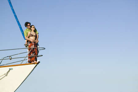 jeopardizing: Couple hugging on bow of boat LANG_EVOIMAGES