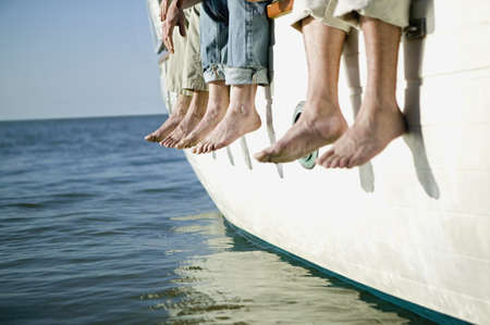 jeopardizing: Bare feet hanging over side of boat