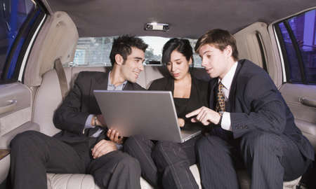 seriousness skill: Three Hispanic businesspeople looking at laptop in limousine