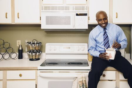 African man eating take out food in kitchen Stock Photo