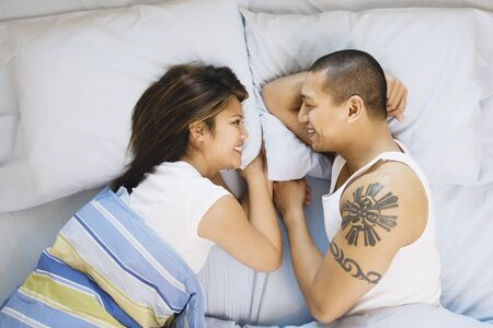 scowling: Asian couple smiling at each other in bed LANG_EVOIMAGES