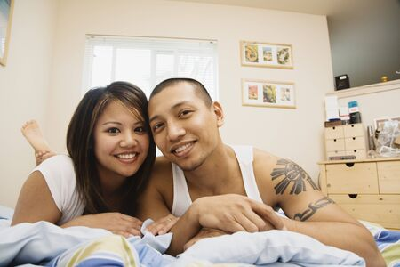 bedcover: Portrait of Asian couple on bed