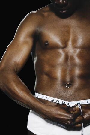 seminude: Semi-nude African man measuring waist LANG_EVOIMAGES