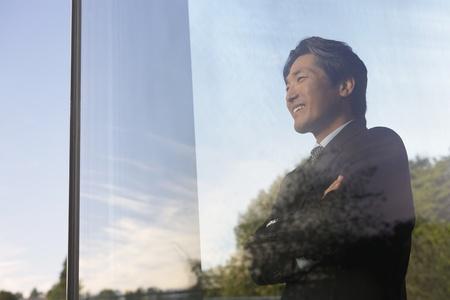 looking through window: Asian businessman looking through window