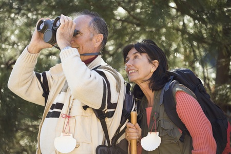 ninety's: Senior couple looking through binoculars in woods