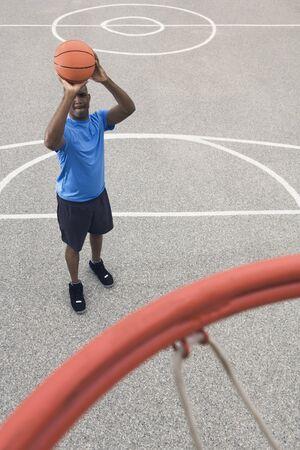 unconcerned: African man shooting basketball LANG_EVOIMAGES