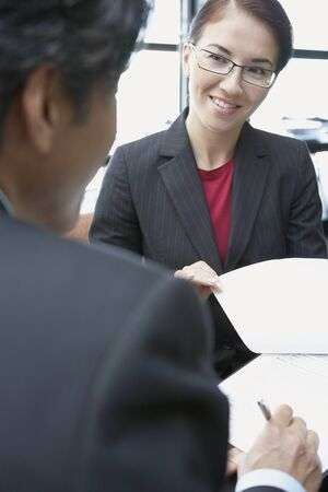 Asian businesswoman discussing paperwork with coworker