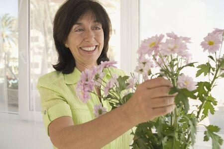 ninety's: Senior woman arranging flowers in vase
