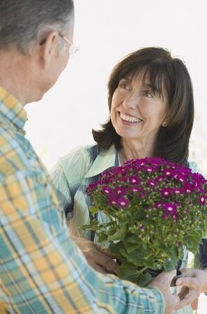 eighty's: Senior man giving wife flowers LANG_EVOIMAGES