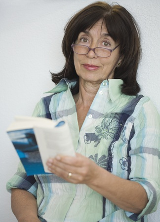 ninetys: Senior woman wearing eyeglasses and reading