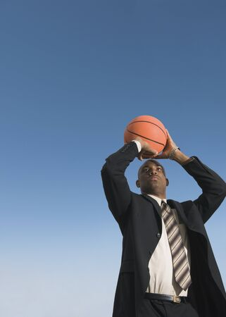 African businessman shooting basketball