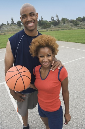 ninetys: Portrait of African couple holding basketball LANG_EVOIMAGES