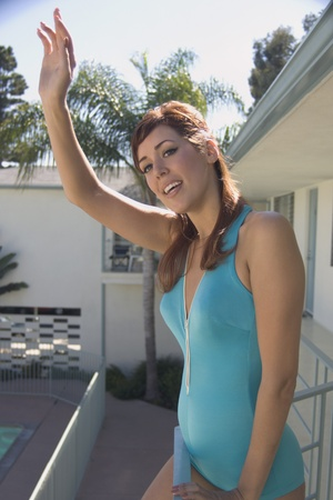balcony: Hispanic woman waving on hotel balcony